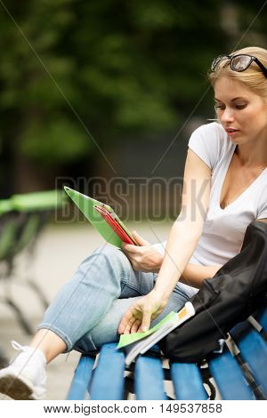 Girl spectacles and with tablet in hand takes book sitting on bench