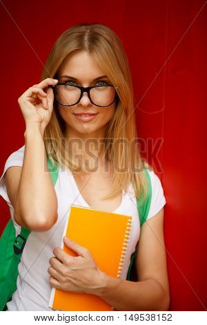 Young woman adjusts glasses on empty background