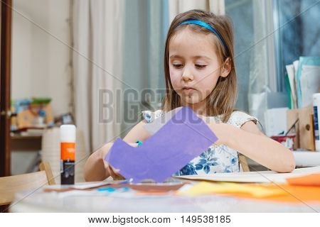 Small girl doing applique at home as homework