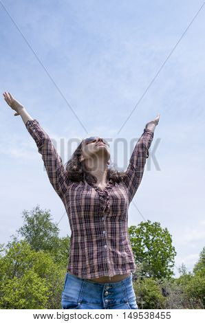 Girl in a shirt lifted her hands up