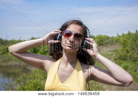 Girl on a background of nature, listen to music with glasses