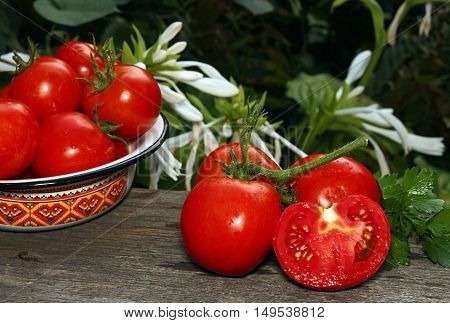 Bunch of fresh ripe tomatoes half of cutted tomato tomatoes in bowl against white flowers background