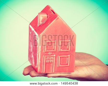 First flat apartment. Step forward concept. Male hand holding little small red house home. Part body man with idea of growing up.