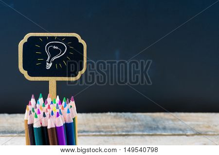 Wooden Mini Blackboard Label With Light Bulb As Idea And Colouring Pencils Over Chalkboard Backgroun