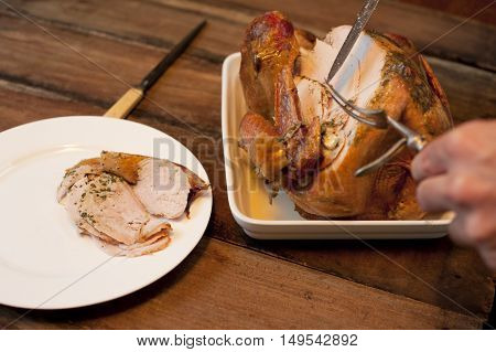 Man carving a delicious roast chicken placing slices of white breast meat on a plate on a wooden dining table