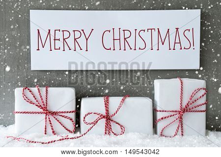 Three Christmas Gifts Or Presents On Snow. Cement Wall As Background With Snowflakes. Modern And Urban Style. Card For Birthday Or Seasons Greetings. Label With English Text Merry Christmas