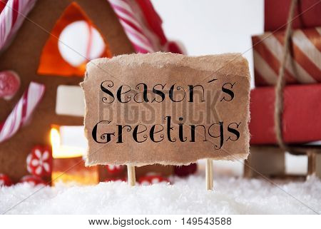 Gingerbread House In Snowy Scenery As Christmas Decoration. Sleigh With Christmas Gifts Or Presents. Label With English Text Seasons Greetings
