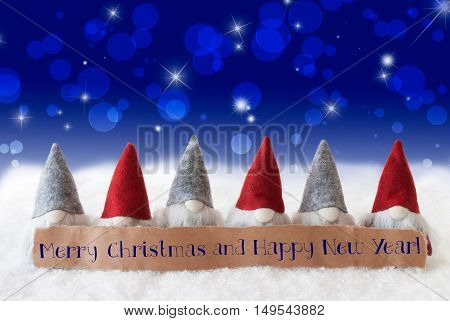 Label With English Text Merry Christmas And Happy New Year. Christmas Greeting Card With Gnomes. Sparkling Bokeh And Blue Background With Snow And Stars.