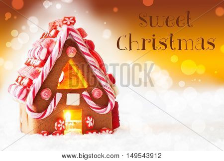 Gingerbread House In Snowy Scenery As Christmas Decoration. Candlelight For Romantic Atmosphere. Golden Background With Bokeh Effect. English Text Sweet Christmas