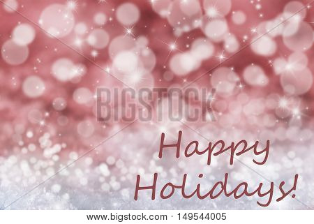 English Text Happy Holidays. Sparkling Red Bokeh Christmas Background Or Texture With Snow And Stars. Copy Space For Your Text Here