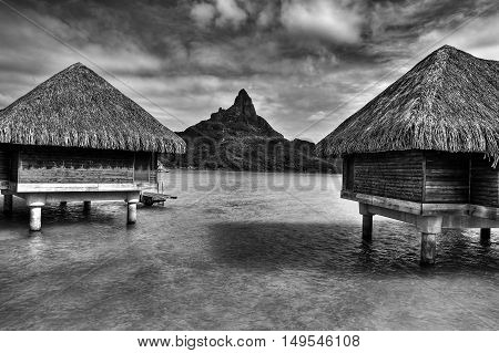 View on Mount Otemanu through lagoon and overwater bungalows on the tropical island Bora Bora honeymoon destination near Tahiti French Polynesia Pacific ocean. Black and white HDR picture.