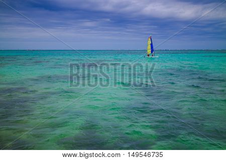 Colorful sailing boat on Caribbean sea with turquoise water under blue sky. Beautiful nature.