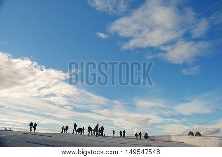 Oslo, Norway - October 25, 2014. Oslo skies. People on the roof of Oslo Opera House against the background of blue skies with clouds.