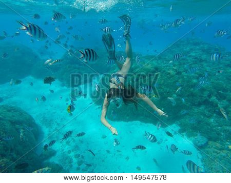 Underwater photo of woman snorkeling and free diving in a clear tropical water at coral reef.
