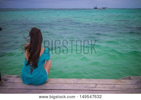 Closeup back view of long hair woman sitting in blue beach dress looking out towards blue ocean and sky.