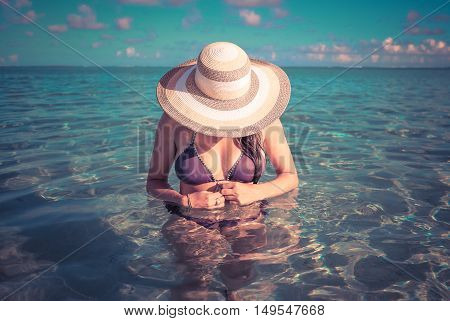 Girl on a tropical beach with hat. Retro style color tones.