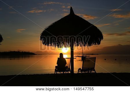 Silhouette of woman sitting on deck chair under umbrella on the beach. Beautiful sunset in the ocean.