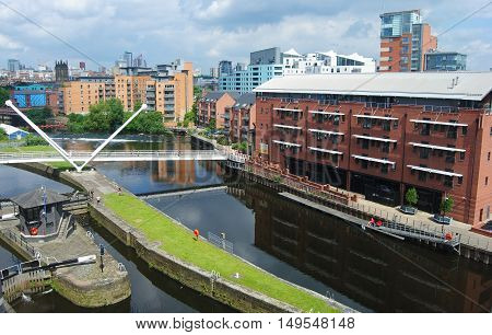 Leeds, United Kingdom - June 23, 2014. River Aire waterfront in Leeds, with residential and commercial buildings, people and bridge.