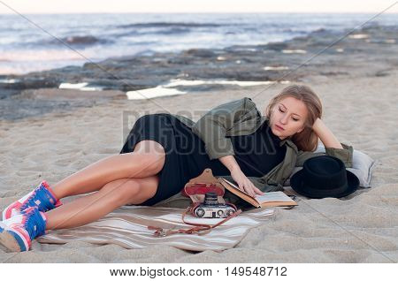 Beautiful woman resting and reading book on the beach in autumn