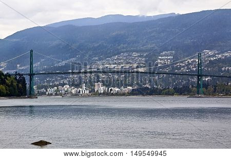 Clear view of the Lions Gate Bridge from Stanley Park with West Vancouver and the Rockies rising in the background. It bridges the inlet between Vancouver Harbour and English Bay.