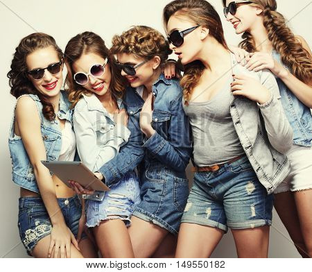 lifestyle and people concept: five hipster girls friends taking selfie with digital tablet, studio shot over gray background