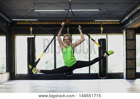 Women doing push ups training with trx fitness straps in the gym. Concept workout healthy lifestyle sport