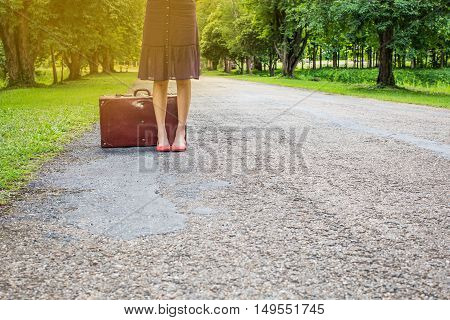 woman with retro vintage luggage on empty street