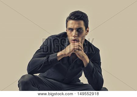 Portrait of a Young Vampire Man with Black Leather Jacket Sitting on Floor