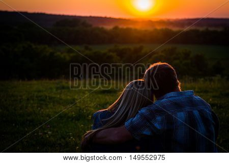 Couple sitting in an open field, watching a sunset, romantic scene. Orange sun with fog in the trees .