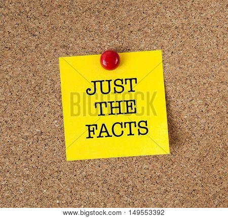 The phrase Just The Facts in red text on a yellow sticky note posted on a cork notice board as a reminder