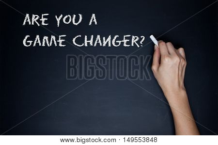 female hand writing the question Are You A Game Changer in white text on a blackboard