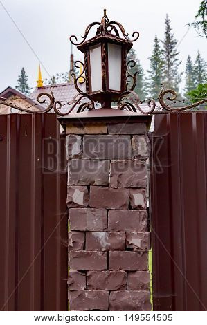 Wrought iron lamps brown with gold leaf on a fence with cobwebs