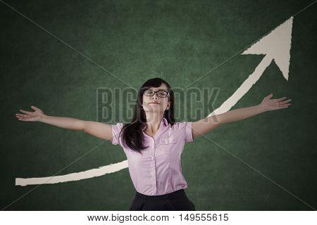 Beautiful woman celebrating for her success with upward arrow on the blackboard