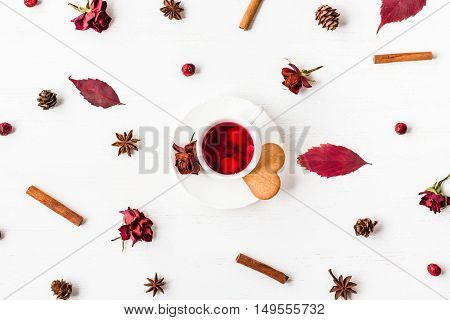 Autumn cup of fruit tea with autumn leaves, cookie, cinnamon sticks, star anise, cones and dried rose flowers. Top view flat lay.