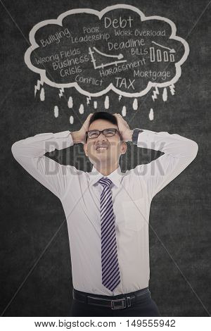 Picture of stressful businessman thinking about solutions for his job problems on the blackboard