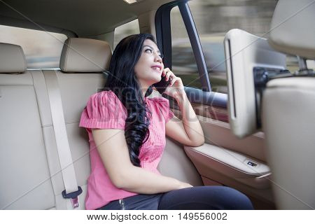 Young businesswoman using cell phone in backseat of car