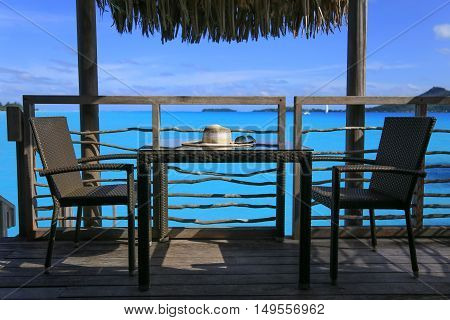 Stylish beach hat and sunglasses over table by the sea. Vacation and travel concept.