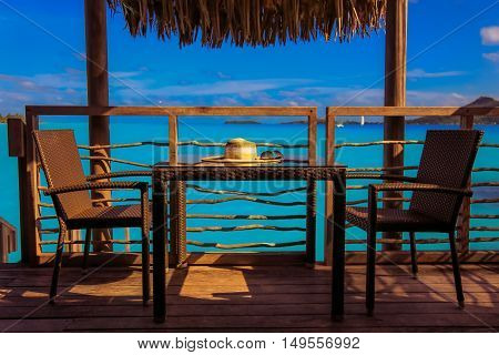 Stylish beach hat and sunglasses over table by the sea. Vacation and travel concept. Retro color style.