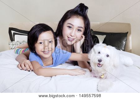 Portrait of beautiful mother hugging her daughter while playing with maltese dog on the bed
