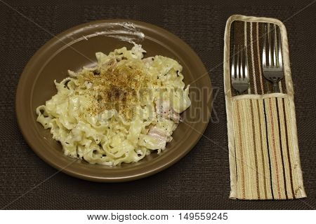pasta carbonara on brown plate with two fork