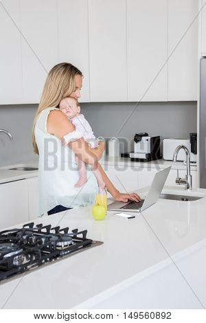 Mother using laptop while carrying baby in kitchen at home