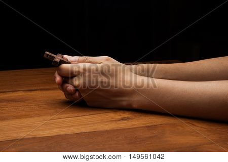 Hands praying with cross on wooden table