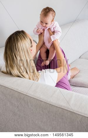 Mother playing with her baby at home