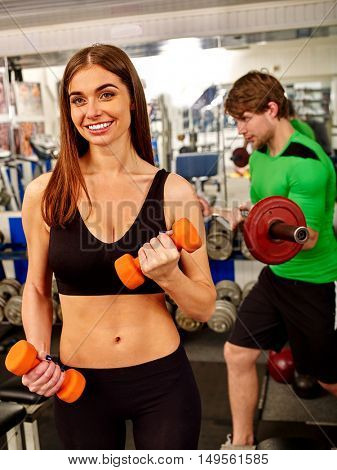 Sport girl working with dumbbells his body at gym. In background strong man with barbell.