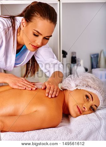 Middle-aged woman take back massage in spa salon with young beautician. Interior with cosmetic.