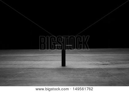 Cross over wood table on a dark background