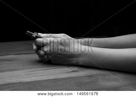 Hands praying with cross on a dark background