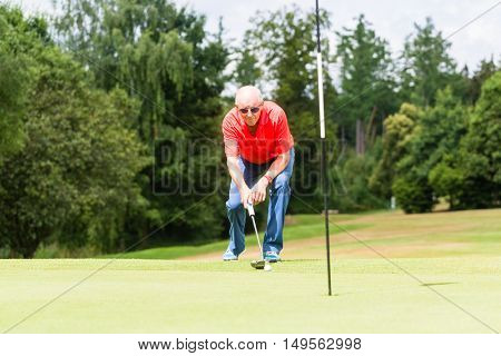 Senior golf player aiming his stroke to the hole