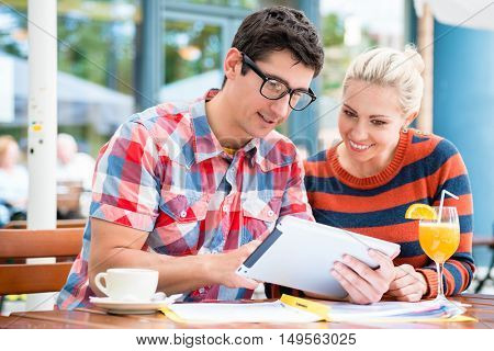 Young couple, woman and man, in street cafe drinking coffee and juice while watching pictures of holidays