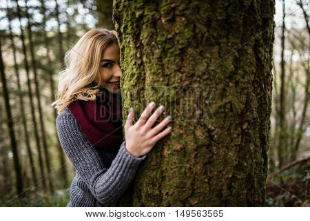 Portrait of beautiful woman hiding behind tree trunk in forest